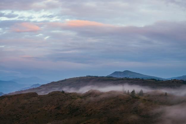 青い夕日や日の出の曇り空の下で木々や山頂のある丘の上に霧のある風光明媚な夜明けの山の風景。木々の間の雲が少なく、日没時の山頂のある大気の風景。