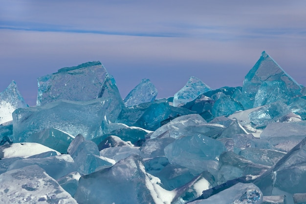 Scenic field of big blockes of broken luminous ice on sky background beautiful winter landscape with icy hummocks