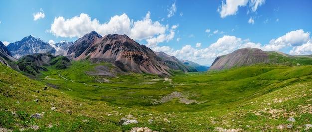日光の下で高原の谷と青い曇り空の下で大きな氷河のある風光明媚な緑青高山のパノラマ風景。緑の山の谷の雲の影