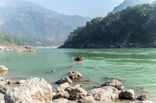 Живописный тур по реке на байдарках. старший каякер на реке ганг. развлечения для туристов в ришикеше