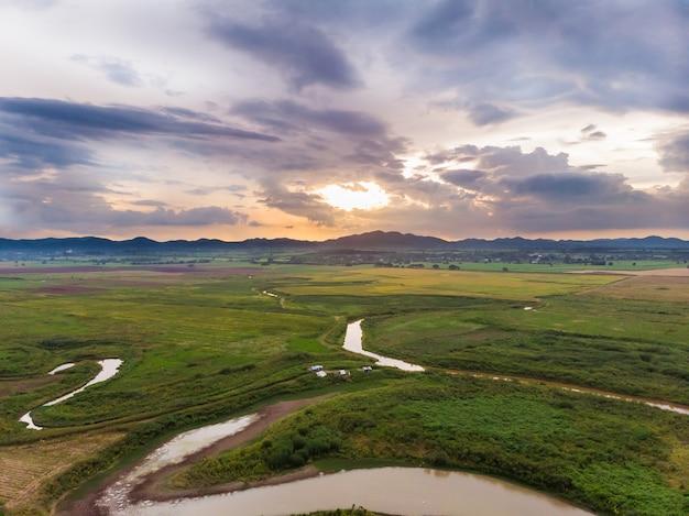 自然の山に対するフィールド川と盆地の風光明媚な風景の空中写真