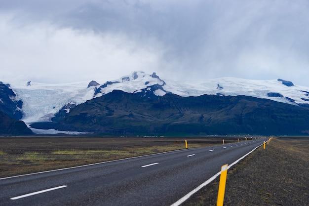 美しい道路のある風光明媚な風景、氷河と雪に覆われた山頂のある山。