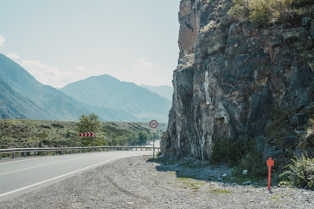 Scenic landscape with speed limit road sign on mountain highway. side view to tract in highlands. beautiful scenery with asphalt road with road markings. highway with solid line and mountain river.