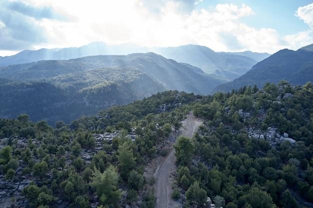 夏の風光明媚な山の風景。緑の木々に囲まれた山々の道路の空中パノラマビュー。