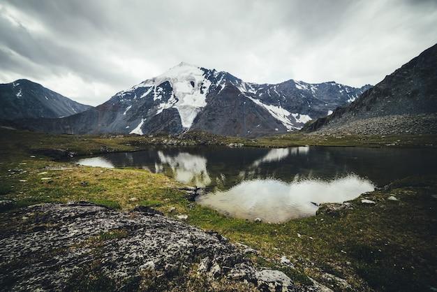 山々に囲まれた氷河湖と灰色の曇り空の下の氷河のある風光明媚な山の風景。雨天時の透明な山の湖と大気の高山の風景。美しい澄んだ高山湖。