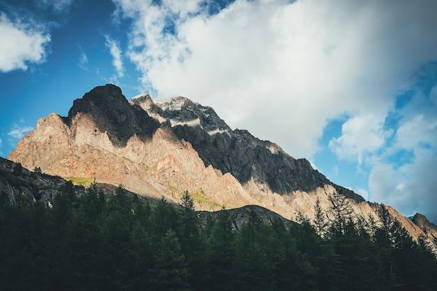 森の上の金色の日光の下で大きな岩のある風光明媚な山の風景。金色の日差しの中で鋭いトップを持つ素晴らしい岩壁。とがった頂点の高い岩山とカラフルな日当たりの良い風景。