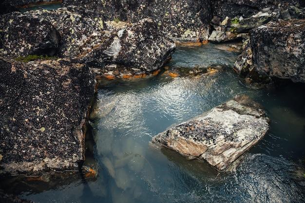 Живописный фон природы бирюзового потока чистой воды среди скал с мхами и лишайниками. атмосферный горный пейзаж с замшелыми камнями в прозрачном горном ручье. красивый горный ручей.