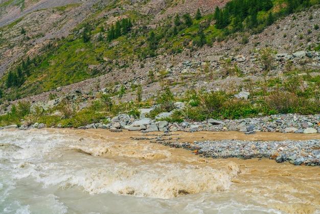 荒々しい色の強力な山川の急流と風光明媚な自然の背景。木々や茂みのある山腹近くの川の速い流れと日当たりの良い鮮やかな自然の背景。カラフルな山の風景