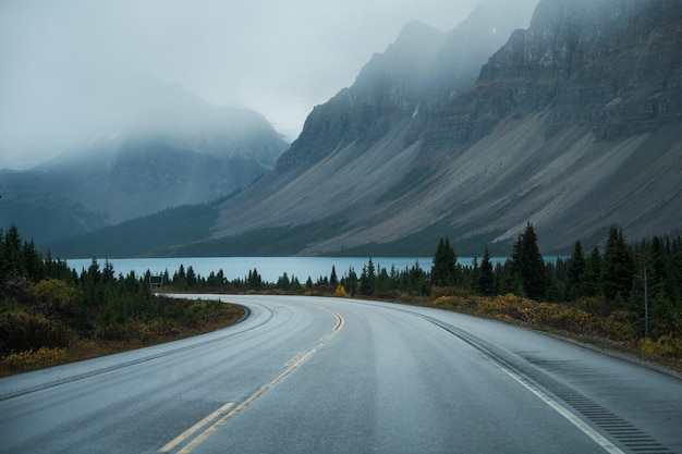 Scenic road trip with rocky mountain and lake in gloomy day