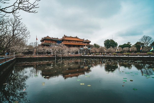 Scenic side view of the meridian gate and a moat surrounding the imperial city with the purple forbidden city within the citadel in hue, vietnam. hue is a popular tourist destination of asia.
