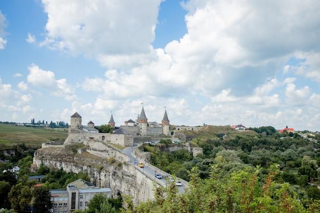カミャネチポディルスキー、フメリヌィーツィクィイ地域、ウクライナの古代の要塞城の風光明媚な夏の景色。 kamyanets-podilskyは、雲が美しい空を背景にロマンチックな街です。