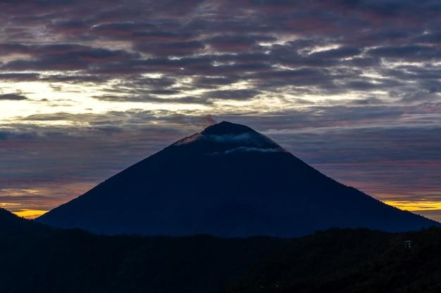 インドネシア、バリ島、キンタマーニのバトゥール火山とアグン火山の風光明媚な日の出。アグン山の頂上からの日の出火山の眺め、自然の風景。火山の山々のシルエットのある曇りの風景