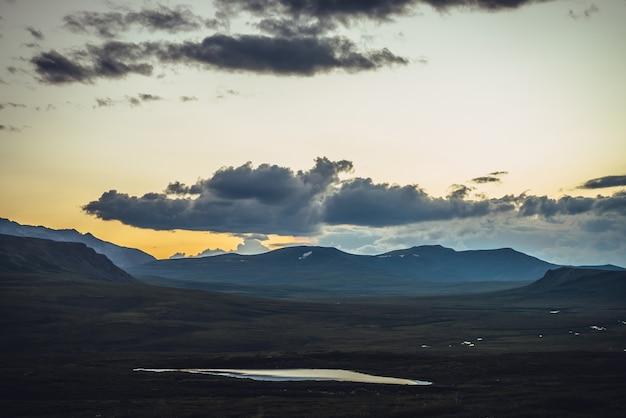 鮮やかなオレンジブルーのグラデーションの空の下に湖のある風光明媚な夕日の風景。曇り空に輝く色のカラフルな山の風景。日の出と湖の美しい山の景色。グラデーションの夜明けの空。
