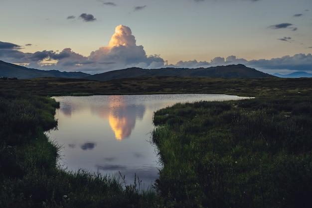 山の湖の上の爆発の形で黄色の大きな雲と風光明媚な夕日の風景。日の出の湖の水に映る恐ろしい巨大な雲。夜明けのグラデーションの空に輝く色の巨大な雲。