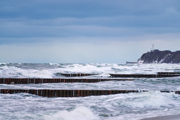 Scenic view of blue sea with foaming waves, cloudy sky and vintage long wooden breakwaters stretching far out to sea