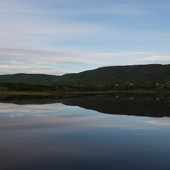 Scenic view of calm river with mountains in background, cheticamp, cabot trail, cape breton island,