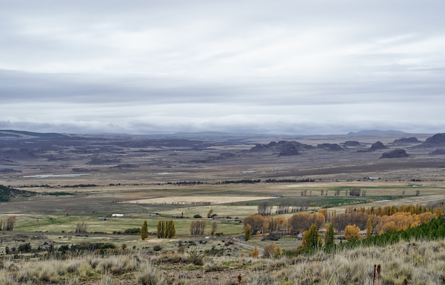 Scenic view of a distant valley with mountains and large meadows for agriculture