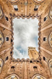 イタリア、シエナの主要なランドマーク、パラッツォパブリックのパティオで下からの美しい景色