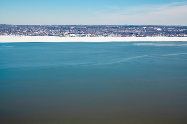 Scenic view over a frozen hudson river on a clear winter day copy space for text