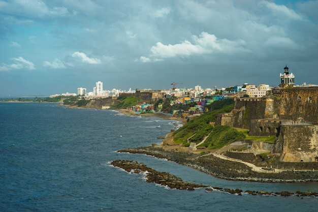 Scenic view of historic colorful puerto rico city in distance with fort in foreground