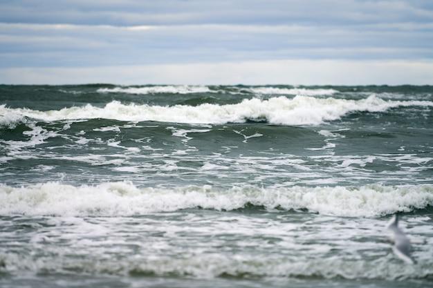 Живописный вид на синее море с бурлящими и пенящимися волнами и красивым облачным небом. пейзаж балтийского моря.
