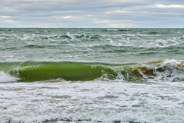 Живописный вид на синее море с бурлящими и пенящимися волнами и красивым облачным небом