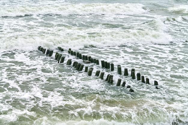 Живописный вид на синее море с пузырящимися и пенящимися волнами. старинные длинные деревянные волнорезы, уходящие далеко в море, зимний пейзаж балтийского моря
