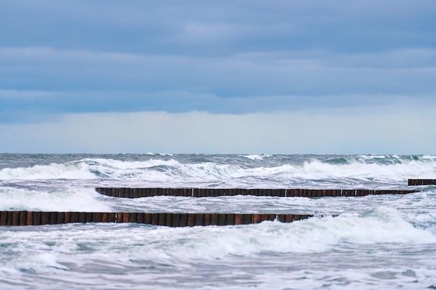 Живописный вид на синее море с пенящимися волнами, облачное небо и старинные длинные деревянные волноломы, уходящие далеко в море.