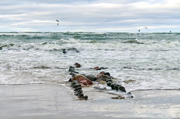 Живописный вид на синее море с пенящимися волнами. старинные длинные деревянные волнорезы, уходящие далеко в море, зимний пейзаж балтийского моря. тишина, уединение, спокойствие и покой.