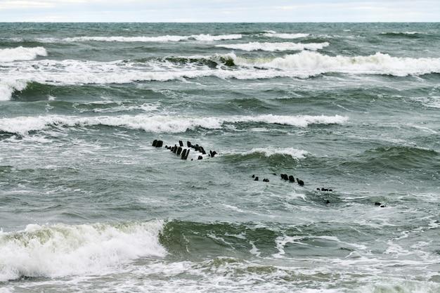 Живописный вид на синее море с пенящимися волнами. старинные длинные деревянные волнорезы, уходящие далеко в море, зимний пейзаж балтийского моря