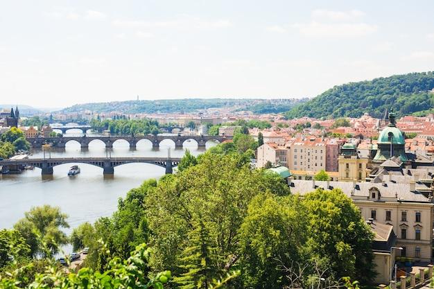 ヴルタヴァ川の橋とプラハの歴史的中心部の美しい景色:赤い屋根のある旧市街の建物とランドマーク。