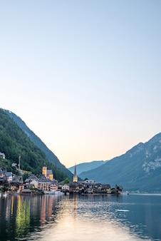 オーストリアのザルツカンマーグート地方、夏の晴れた日にオーストリア アルプスのハルシュタット湖に映る有名なハルシュタット湖畔の町の風光明媚な景色