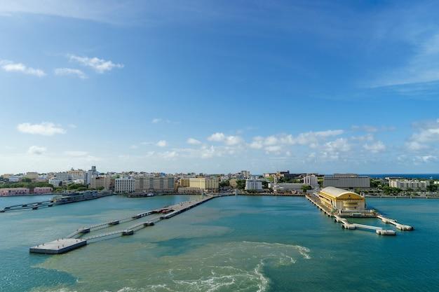 전경의 항구와 바다에서 거리에있는 역사적인 다채로운 푸에르토 리코 도시의 경치를 볼 수 있습니다.