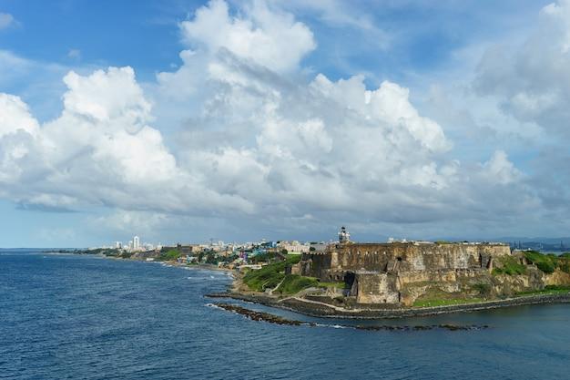 바다에서 전경에 요새와 거리에있는 역사적인 다채로운 푸에르토 리코 도시의 경치를 볼 수 있습니다 (크루즈 선박)