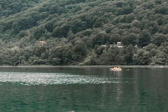 Scenic view of idyllic lake near the green mountain