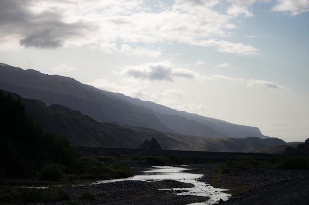Живописный вид на гору среди снежных гор возле реки в торсморке, исландия.