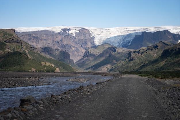 Живописный вид на горную дорогу среди снежных гор у реки в торсморке, исландия.