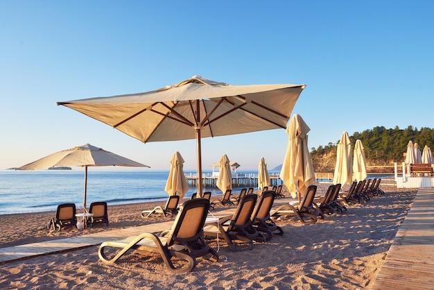 Живописный вид на частный песчаный пляж с шезлонгами и парасоками на море и горы. курорт.