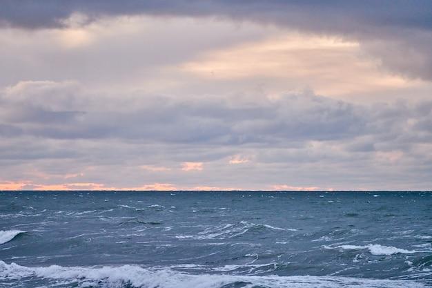 Живописный вид на фиолетовое облачное небо и синее море с пенящимися волнами. ветреная погода, красивый вечерний пейзаж балтийского моря.