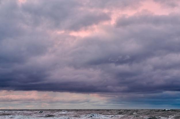 Живописный вид на фиолетовое облачное небо и синее море с пенящимися волнами