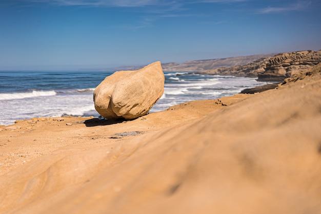 澄んだ空と崖の近くの岩の風光明媚な景色