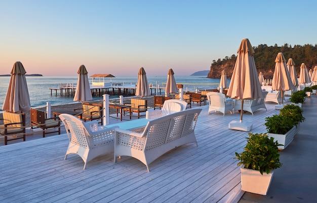 일광욕 용 침대와 파라솔이 비치 된 해변의 모래 해변이 바다와 산을 향해 펼쳐집니다. 호텔. 의지. tekirova-kemer. 터키
