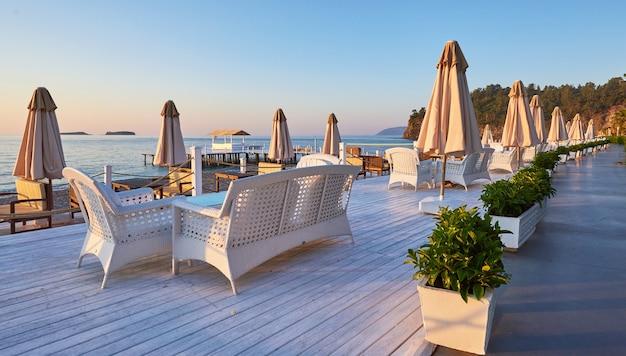 Живописный вид на песчаный пляж на пляже с шезлонгами и зонтиками, открытыми против моря и гор. гостиница. курорт. текирова-кемер. турция
