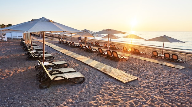 サンベッドとパラソルが海と山に向かって開いているビーチの砂浜の美しい景色。ホテル。リゾート。ケメロボ・ケメル。七面鳥