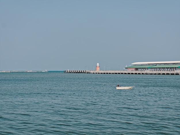 Живописный вид на небольшую лодку и башню с горизонтом над морской водой