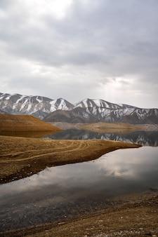 Живописный вид на азатское водохранилище в армении с заснеженным горным массивом