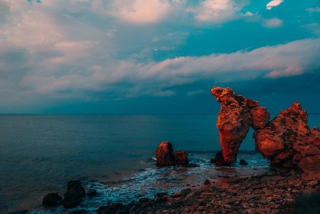 Живописный вид на море, каменистую береговую линию и песчаный пляж, туристический фон на открытом воздухе, синяя отделка