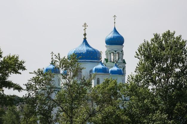 Живописный вид на христианскую церковь с голубыми куполами и золотыми крестами за деревьями в торжке.