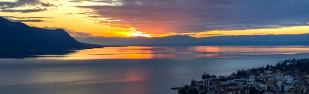 Scenic view of sunset over the leman lake with yellow sky with clouds and alps mountains, montreux, switzerland.