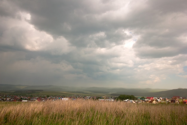 Scenic view with dark stormy sky and countryside
